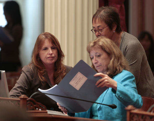 Democratic state Sens. Noreen Evans of Santa Rosa, left, Ellen Corbett of San Leandro, right, and Carol Liu of Pasadena, standing, look over papers at the Capitol in Sacramento.
