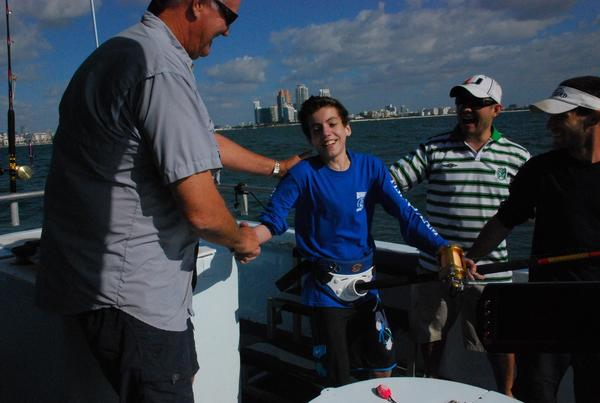 Yan Andrade is congratulated by Capt. Wayne Conn after catching his first fish, a 17-pound jack crevalle.