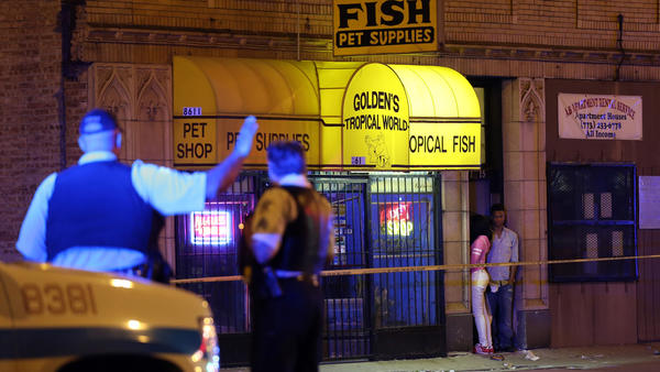 Officers stand near the scene of a fatal shooting at the corner of 86th Street and Ashland Avenue Thursday, May 16, 2013, in Chicago. A 15-year-old male was shot and transported to a hospital, where he was later pronounced dead.