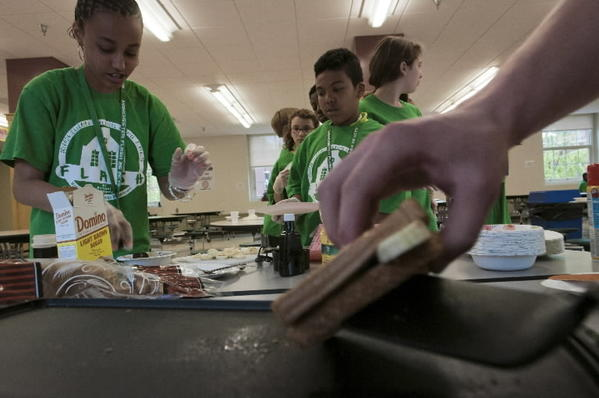 Tiana Rawlings (L) prepares a grilled banana sandwich during the Friends Learning Athletics Service & Health (FLASH) program at Bennet Academy.