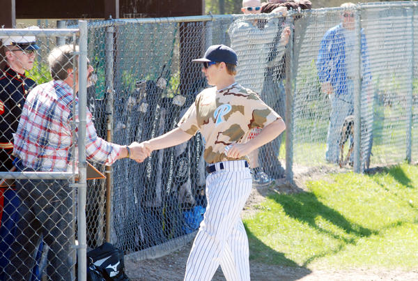 Petoskey junior Nick Strobel (right) presents Dan Robinson with a game ball as Marine Corps Sergeant recruiter Chris VanBeekom (left) looks on during the Northmens Military Appreciation Game at Turcott Field Thursday. Robinson is the father of 1995 Petoskey High School graduate, former Northmen baseball player and Navy Seal Heath Robinson, who died in August 2011 in a CH-47 Chinook helicopter crash in Afghanistan. The Northmen honored Robinson and all military prior to the game.