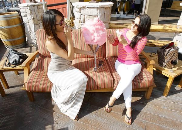 Dominique Llanes, left, and Gina Archie enjoy a cotton candy tower in one of lounge areas at the newly opened Saddle Ranch Chop House at the Triangle in Costa Mesa.
