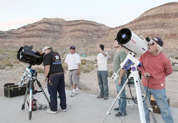 Stargazers look at the moon and visible planets before the sun sets during a public star party at the Mojave National Preserve on Saturday, May 11, 2013. Members of the Old Town Sidewalk Astronomers, made up of residents from the San Gabriel Valley, have arranged the free events in the Mojave desert since 2008.