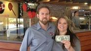 Jason Harris and Kara Seelye display the first dollar made at their new restaurant in Lighthouse Point. Photo by Drew French, Your Pie founder