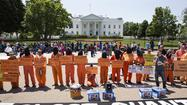 Activists wearing orange jumpsuits mark the 100th day of prisoners' hunger strike at Guantanamo Bay during a protest in front of the White House in Washington