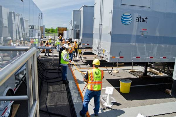 Crews lay wires between disaster response trailers during an AT&T drill outside of Rentschler Field in East Hartford.