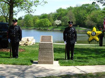 Downers Grove police officers stand guard next to a decorative wreath with Officer Richard Barth's badge number during an annual memorial.