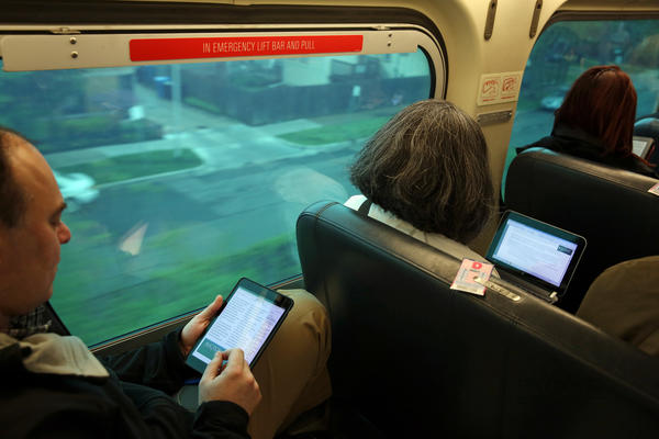 David Kaufman of Wilmette, left, uses his iPad as other train passengers use their wireless devices on an inbound Metra train in Chicago.