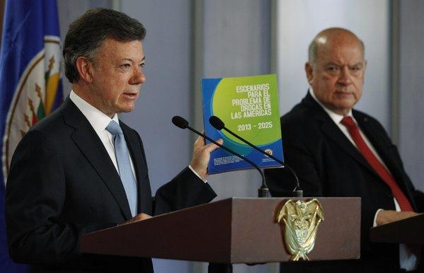 Colombian President Juan Manuel Santos, left, holds a copy of a study on the illicit drug trade presented by Organization of American States Secretary-General Jose Miguel Insulza, right, during a news conference in Bogota, Colombia.
