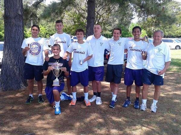The Menchville boys tennis team celebrates the 2013 Eastern Region championship they won by defeating Ocean Lakes 5-0 on May 17 at Huntington Park. Stuart McCroskey, kneeling, holds the trophy. Standing are Jake Fields, Brandon Pingley, Matt Strehle, Jordan Moore, Austen Delnicki, Steven Gangitano and Coach Steve Sipe.