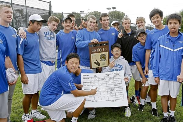 San Marino High School's tennis player James Wade, center, holds the 2013 CIF Div. II, Boys Tennis Championship trophy along with the rest of the team after defeating Palm Desert High School at the Claremont Club in Claremont, Ca., on Friday, May 17, 2013. The team won 13-5.