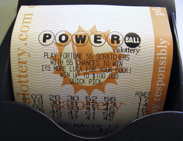 A Powerball lottery ticket is printed out of a lottery machine after purchase at a convenience store in Encinitas, California.