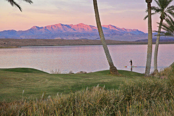 Stand-up paddleboarding, a popular water sport, is available from sunrise to sunset on the calm waters of Lake Las Vegas.
