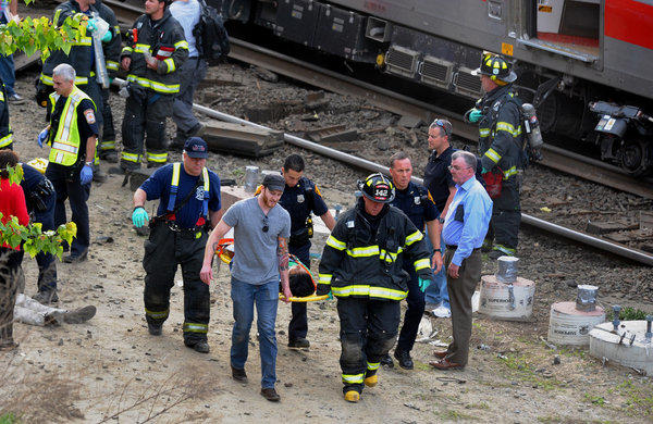 Injured passengers are taken from the site of a collision between two commuter trains near Fairfield, Conn.