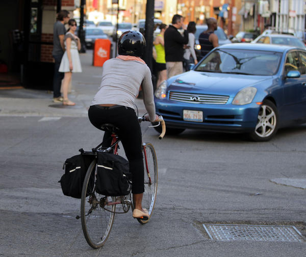 A cyclist rides along side a crosswalk and against the flow of traffic at Damen and North Avenues in Chicago.
