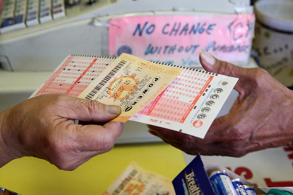 A customer purchases a Powerball ticket Friday in San Francisco, joining people across the state lining up for a chance at the monster jackpot.