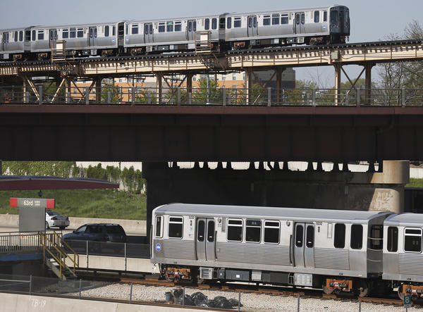 "A CTA northbound Green Line ""L"" train, top, and a southbound Red Line ""L"" train, bottom, pass each other at the Dan Ryan Expressway near the CTA Red Line 63rd Street station in Chicago on Tuesday, May 14, 2013. With the $425 million Red Line reconstruction project, many commuters will be rerouted via buses to the Green Line."