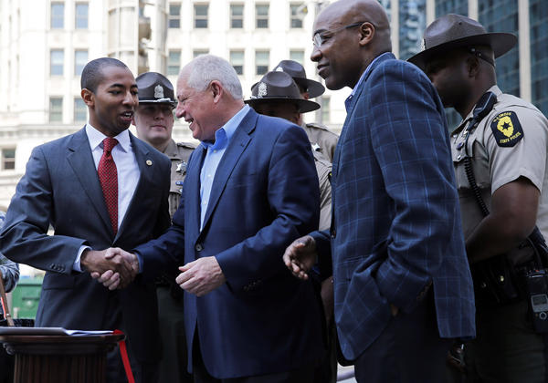 Gov. Pat Quinn shakes hands with State Rep. Christian Mitchell on Saturday after signing legislation which toughens penalties for individuals who use social media to organize group violence in Illinois.