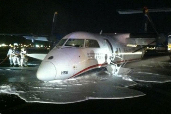 Emergency personnel spray foam on a U.S. Airways Express commuter plane after it made a belly landing at Newark Liberty International Airport.