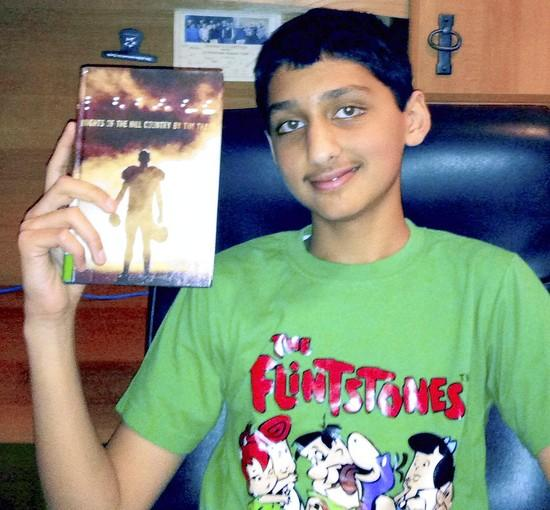 "Nikhil, 7, of Allentown holds one of his latest reads ""Knights of the Hill Country"" by Tim Tharp"