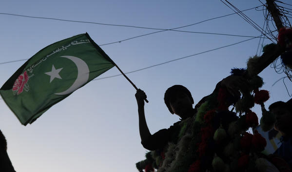 A supporter of Pakistan Muslim league Functional (PML-F) holds a flag as part of election campaign in Karachi on May 4.