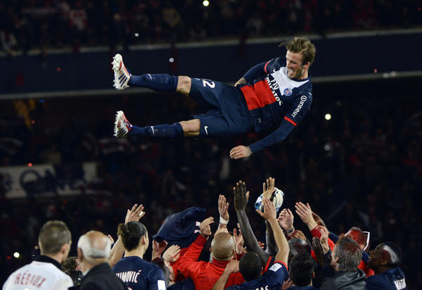 David Beckham is thrown in the air by teammates after a French L1 football match between Paris St Germain and Brest.