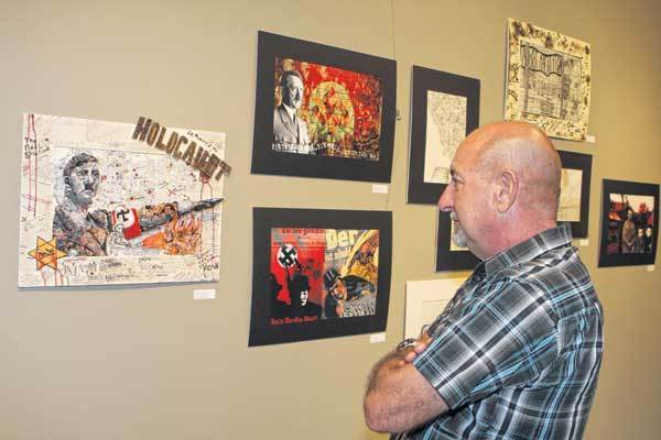 Michael Gerndt looks at a piece of art that his granddaughter made for an art and essay contest for the Holocaust Museum at Temple Beth-El. There were more than 60 entries for the contest.