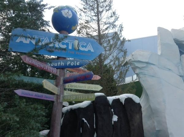 "Mile markers at the entrance to SeaWorld's Antarctica show the distance to a wide range of locations. The globe atop indicates ""You are here,"" here being the South Pole."