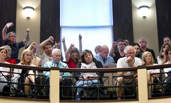 Fluoride opponents and proponents gesture during a Portland City Council meeting in 2012.