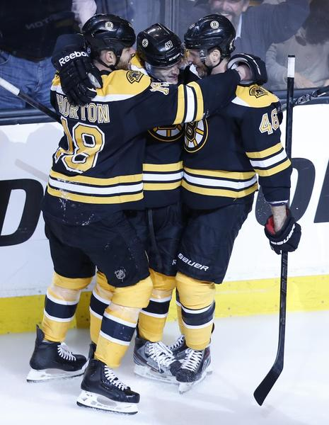 The Bruins' Torey Krug is hugged by Johnny Boychuk and David Krejci after a goal during first period.