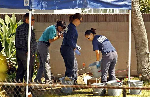 Ed Winter, assistant chief at the Los Angeles County Coroner's Office, left, works with investigators in the backyard of a home in Pico Rivera where Joseph Rubalcaba's body was found.