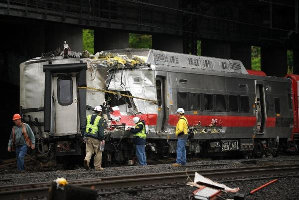 Crews work at the site of a train derailment in Bridgeport, Conn., that left dozens injured. The tracks require extensive repair; commuters were urged to carpool or stay home.