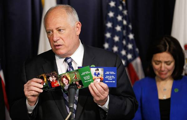 Gov. Pat Quinn holds photographs of three boys killed in the Newtown, Conn., school shooting as Newtown parent Francine Wheeler, right, looks down Sunday during a news conference at the Thompson Center in Chicago. Two other Newtown parents joined a push in Illinois to ban high-capacity ammunition magazines statewide.