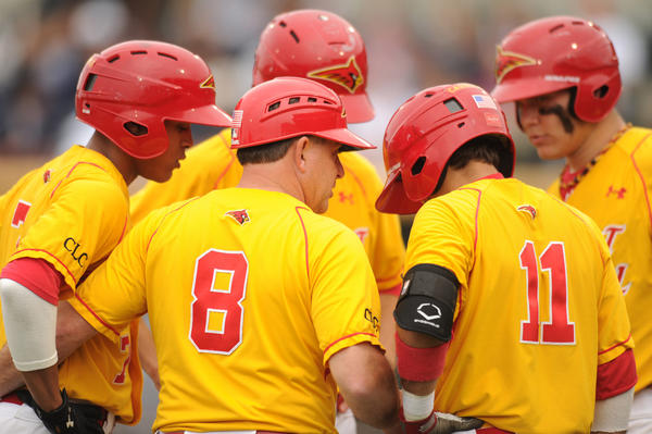 Calvert Hall third base coach Brooks Kerr huddles his players together to discuss base running strategy during a timeout.