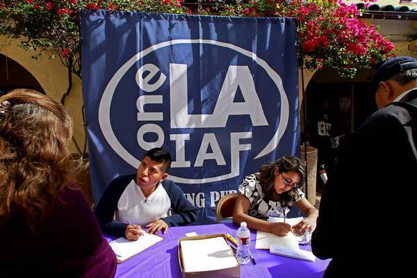 Volunteers Raoul Vargas, left, and Jacqueline Soriano sign people up for Medi-Cal and Healthy Way L.A. in March.