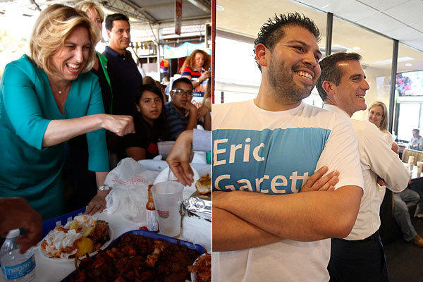 Mayoral candidate Wendy Greuel goes in for a fist bump at the Port O' Call in San Pedro. Rival Eric Garcetti poses with volunteer Richard Granados at Straw Hat Pizza in Chatsworth.