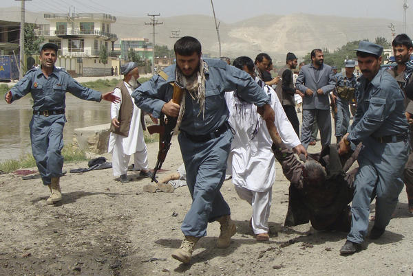 Afghan police officers evacuate a wounded person after a suicide bomber struck the offices of Mohammad Rasoul Mohseni, chief of the Baghlan provincial council, in Pul-e-Khumri.