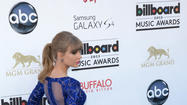 "Taylor Swift rocked a sparkly blue mini dress by Muhair Zurad, with cutouts across her shoulder blades, when she accepted eight awards, including artist of the year, at the Billboard Music Awards at the MGM Grand in Las Vegas on Sunday. She also wore Jimmy Choo ""Suki"" platform sandals, according to a news release."