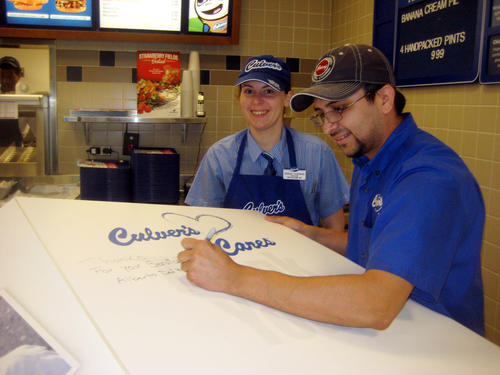 Alberto Del Hoyo, manager of Culver's Restaurant, 7310 Dempster, Morton Grove, is the first to sign a giant card that customers will sign this week to honor veterans in preparation for Memorial Day, while assistant manager Jesse Tavernier looks on. All Chicagoland and NW Indiana Culver's restaurants will donate 10% of its proceeds this Tuesday, May 21, to Honor Flight Chicago, a non-profit organization that flies World War II veterans to the WWII Memorial in Washington, DC.