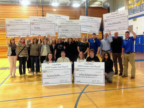 District 230 staff hold the checks they recieved from the District 230 Foundation grant program.