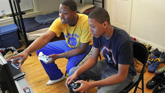 Quron Davis plays a video game with his brother Quentin in a February file photo.