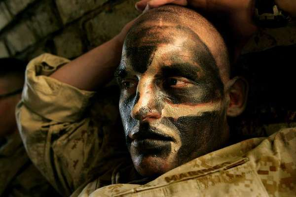 "During the fierce battle in Najaf, Iraq, in 2004, Carolyn Cole shot this portrait of a resting Marine, titled ""War Paint."""