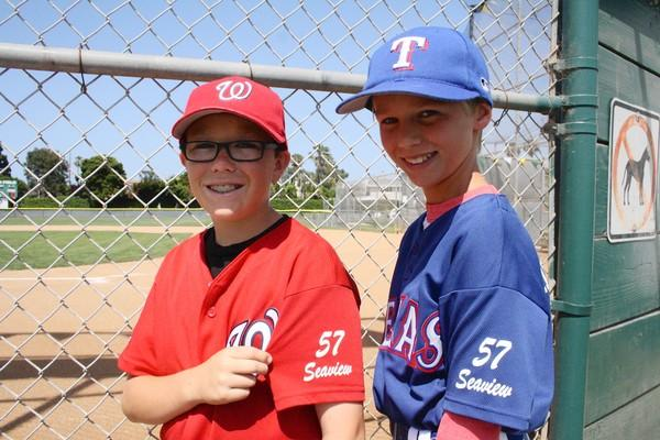 Donovan Phillips, 11, Sowers Middle School, left, and Sean McCrimmon, 11, Sowers Middle School, display the number 57 the Seaview Little League teams wear in honor of Greg Willard, a former NBA referee and Huntington Beach resident who was a member of the Seaview Little League board.