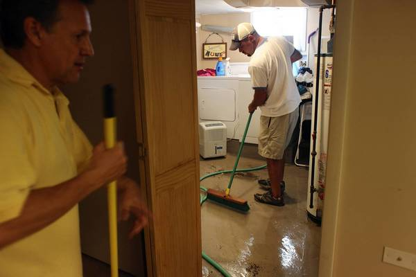 In this 2011 photo, Phil Krawiek, left, and Chris Stukel try to get rid of the excess water in the basement of Stukel's mother, Olivia, on the 7800 block of West Thorndale Avenue in Park Ridge.