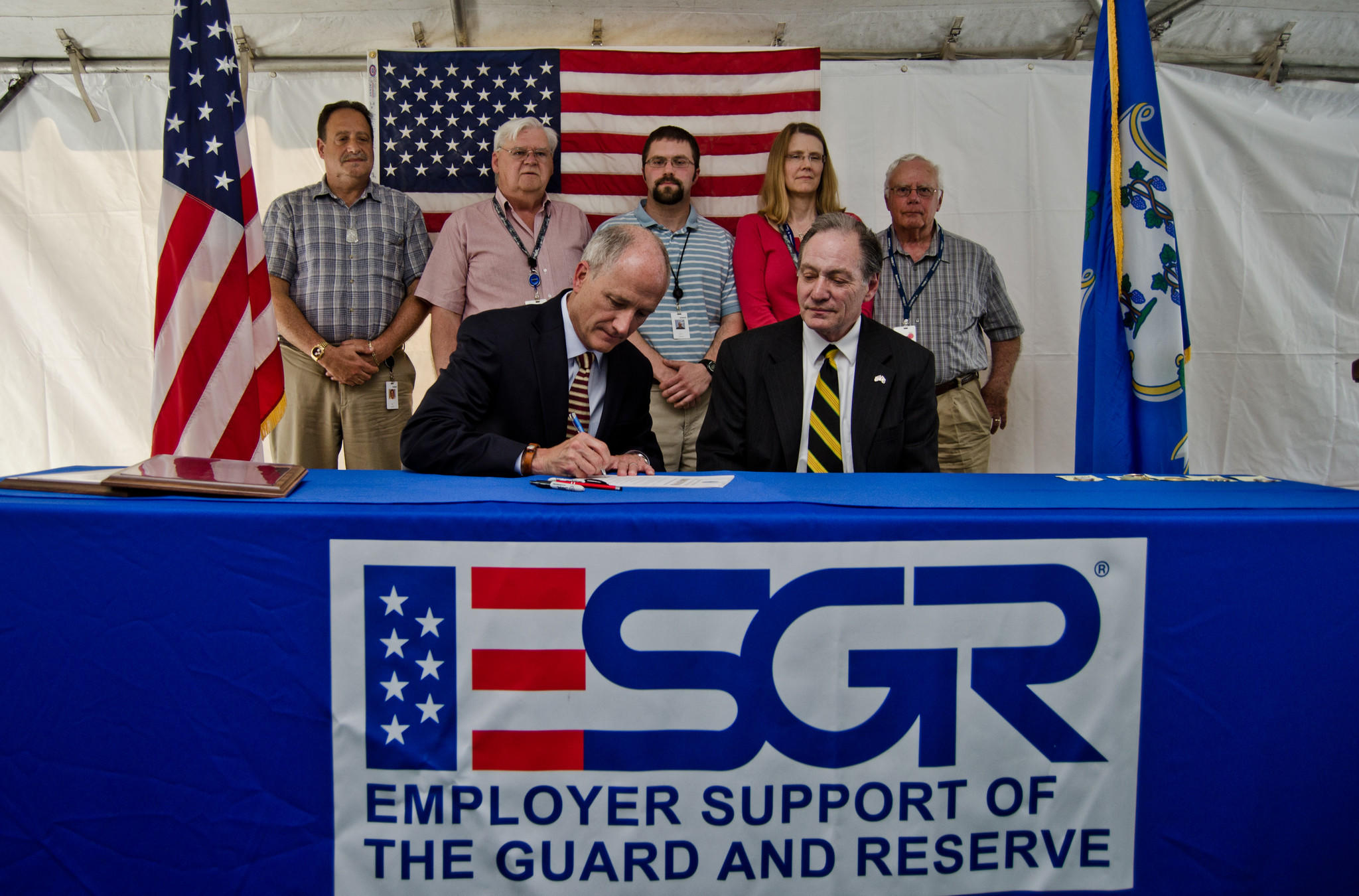 Kaman CEO Neal Keating signs a support statement the Pentagon's Employer Support for the Guard and Reserve program, seated next to the program's local official, Ted C. Graziani. Behind them stand Kaman employees who, as veterans, have served in different branches of the military: (from left) Joe Mazza, Air Force; Bill Houlberg, Army; Kyle Korab, Navy; Valerie Johnson, Marines; Joe St. Jean, Coast Guard.