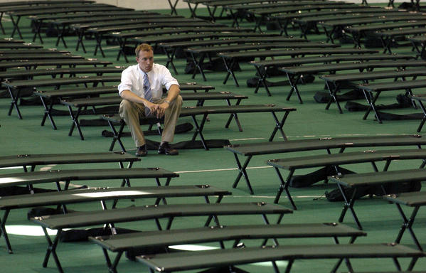 FROM THE ARCHIVES: BALTIMORE,MD--SEPTEMBER 6, 2005--Adam May a news reporter for WJZ 13 , sits on one of the hundreds of beds that have been set up at the Du Burns arena for hurricane Katrina victims, while he waits to do his report on the story. Digital IMage # 0085.