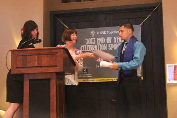 High school graduate Jose Santos from Shalimar Community Teen Center receives his Good to Great scholarship from Mary Hendricks, Woman of Vision chairwoman, and THINK Together High School Career and College Resource Specialist Bethany Fernandez .