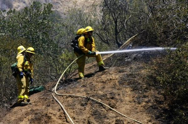 Firefighters douse the hillside in Burbank on Monday as they worked to contain a brush fire that started near DeBell Golf Club.