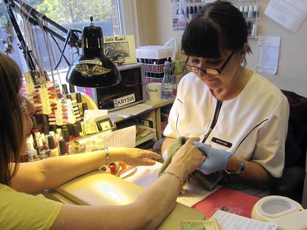 Krystyna Krell performs a manicure at Renu Day Spa in Deerfield on May 15. Spa owner Anna Pamula says she pays her employees more than minimum wage, and would support a state measure to increase the level from $8.25 to $10 per hour.