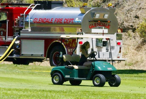 Some players at DeBell Golf Club on Monday continued on despite the nearby firefighting operation.